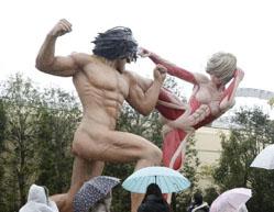 <「ユニバーサル・クールジャパン」で「進撃の巨人」のエリアに再現された巨人が格闘する場面>